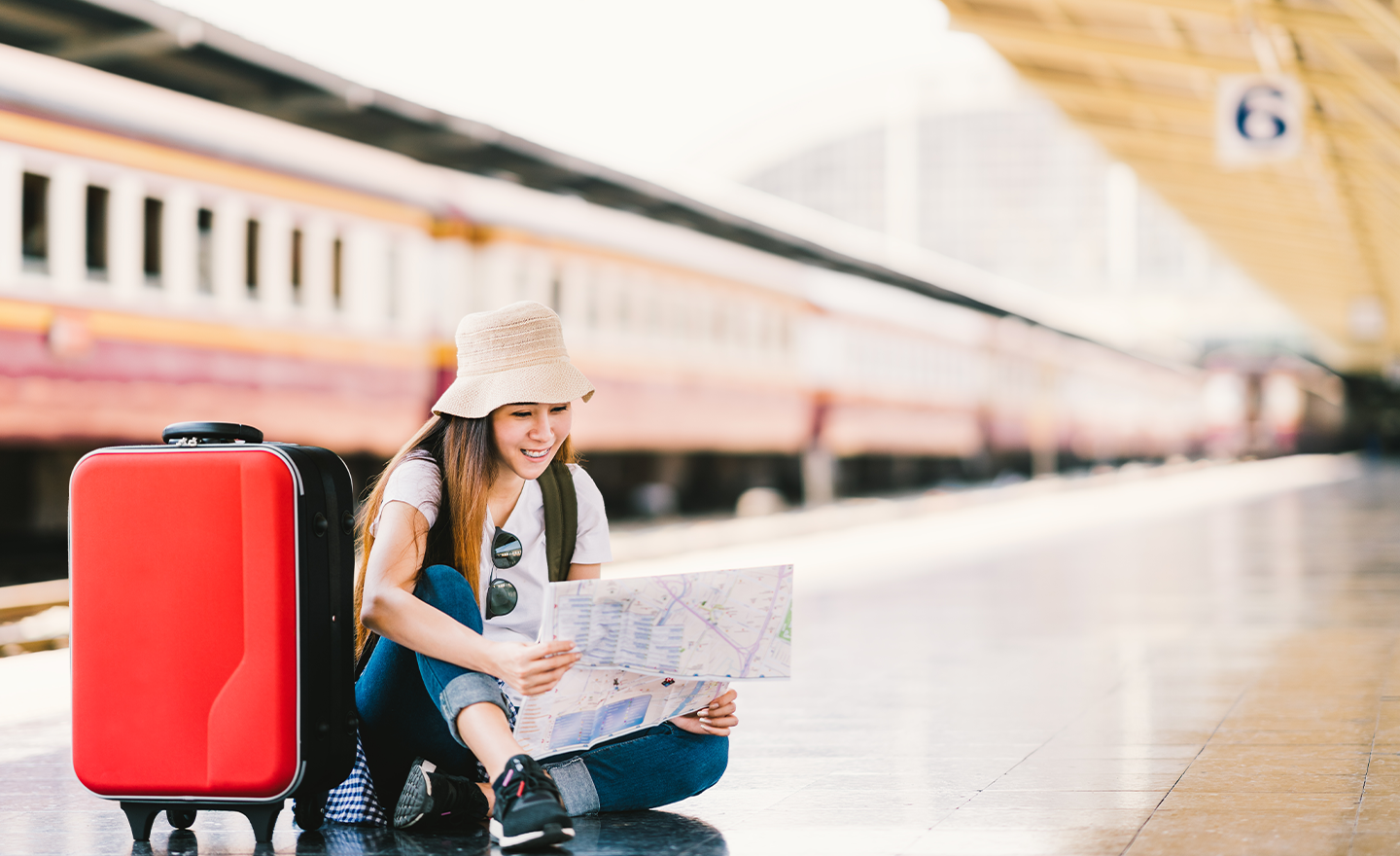 Young woman wearing hat sits on train platform with train behind her. She's looking at a map with her travel bag on the platform beside her.