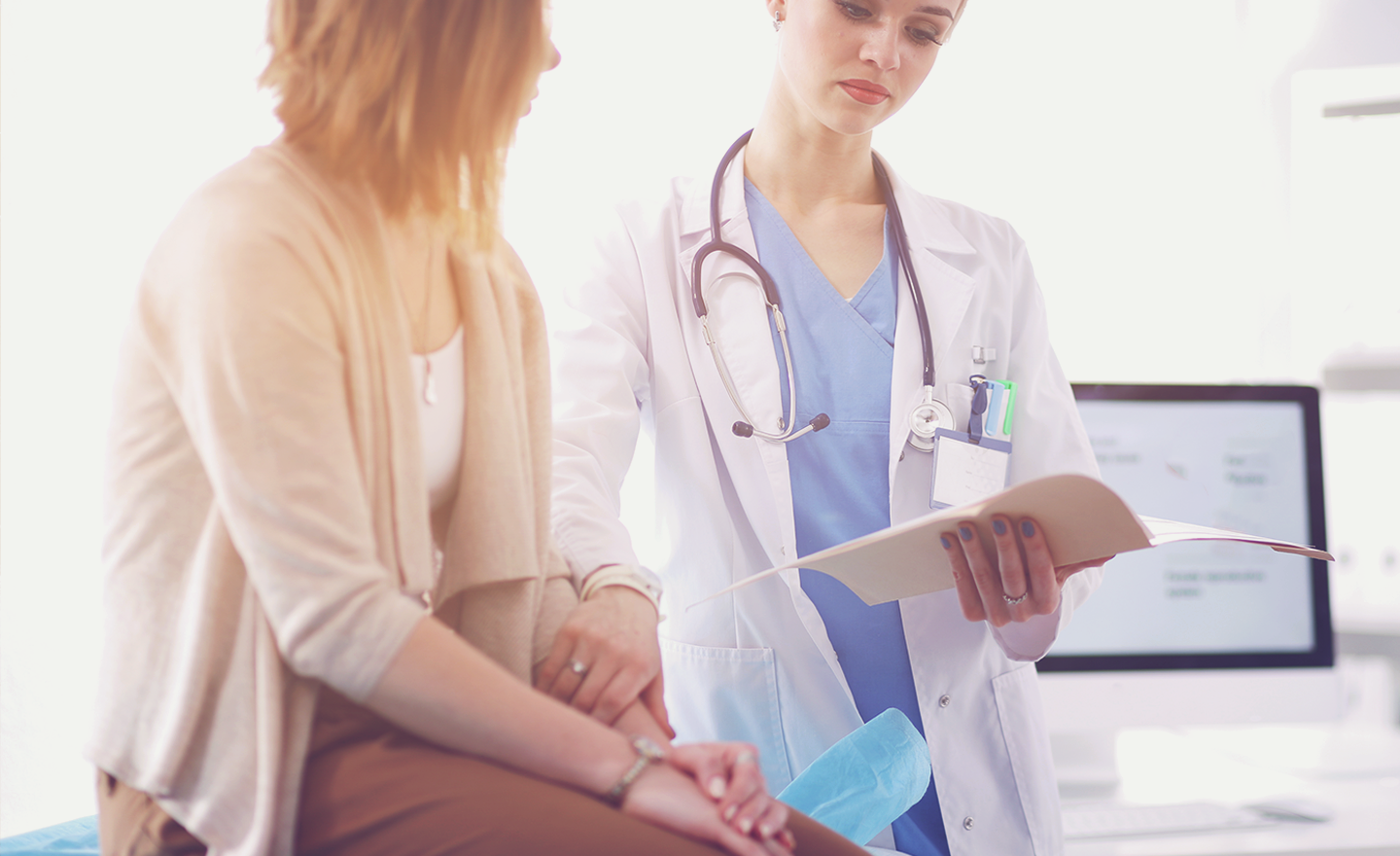 Female doctor goes over medical information in doctor's office with female patient
