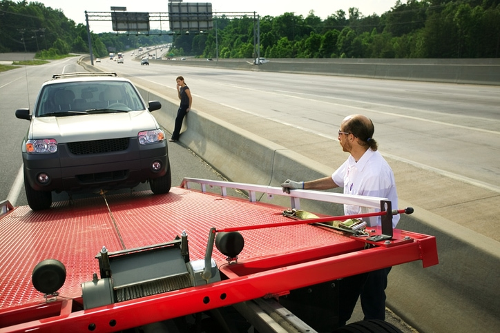 Man towing a women's car off of a freeway