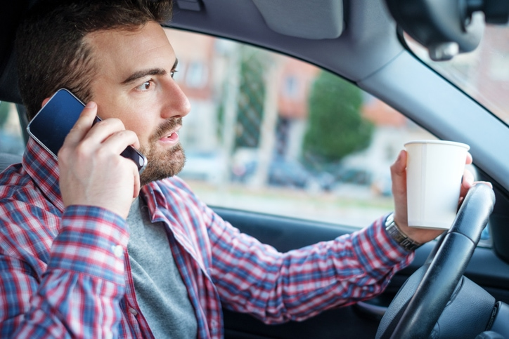 Man distracted while driving with a coffee in one hand and talking on the phone with the other hand