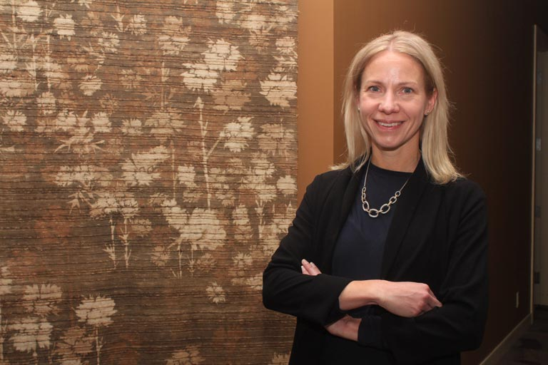 Dawn Ladds, vice president of commercial sales for Western Financial Group, stands in front of a patterned curtain with crossed, relaxed arms