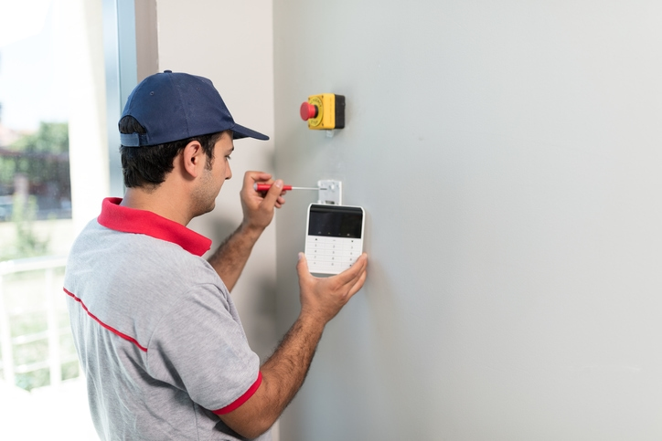 Man installs security system control panel on to home's wall.