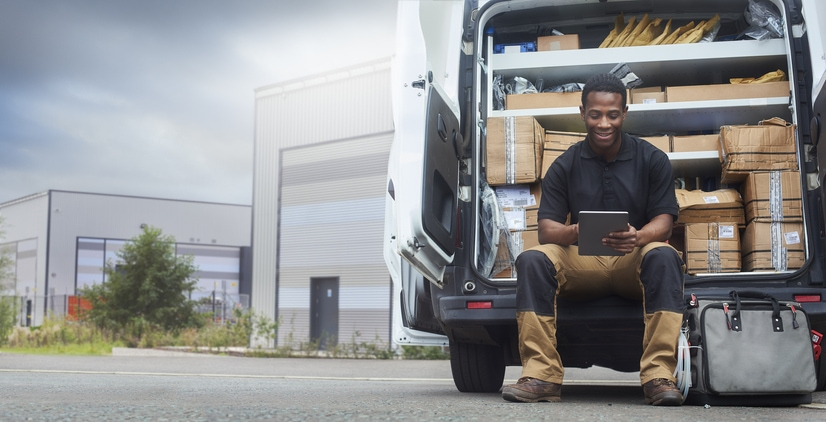 Young man sitting on the back bumper of his van looking at a tablet