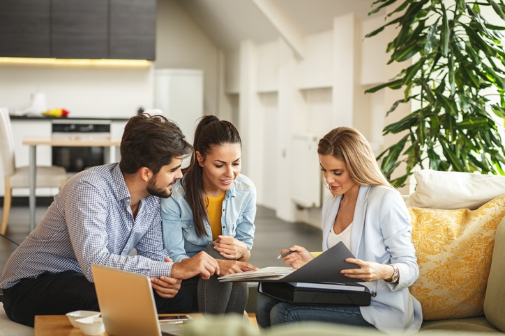 Young couple sitting with an Insurance Adviser going over their home insurance policy