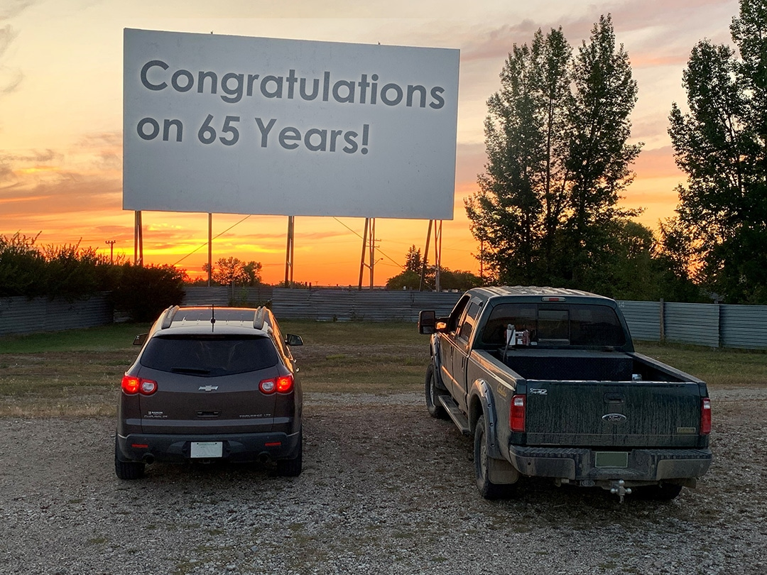 Two vehicles in front of a large drive-in movie theatre screen with the message Congratulations on 65 years