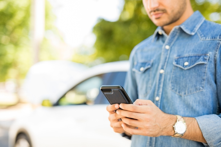 Young man looks at his phone outside next to his car