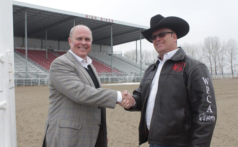 Rod Cunniam, Western Financial Group's head of digital and brand, shakes hands with Bryan Hebson, marketing director with the World Professional Chuckwagon Association (WPCA).