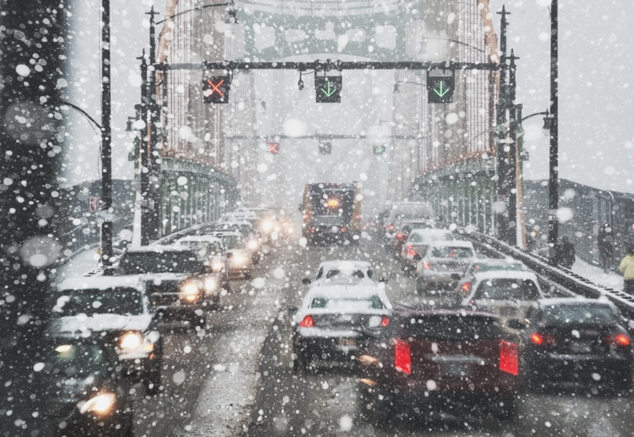 Cars driving across a bridge in a snow storm