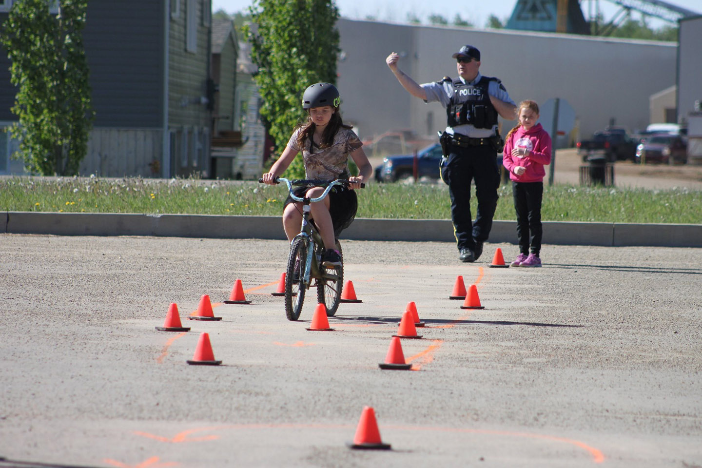Sergeant Greg Beach assists a young rider during a bicycle safety rodeo